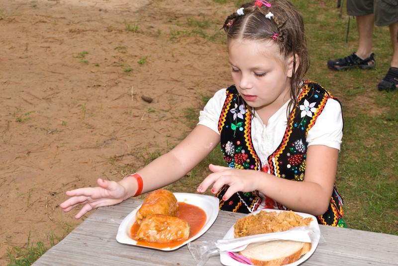 Young lady enjoying a meal of golabki and bigos