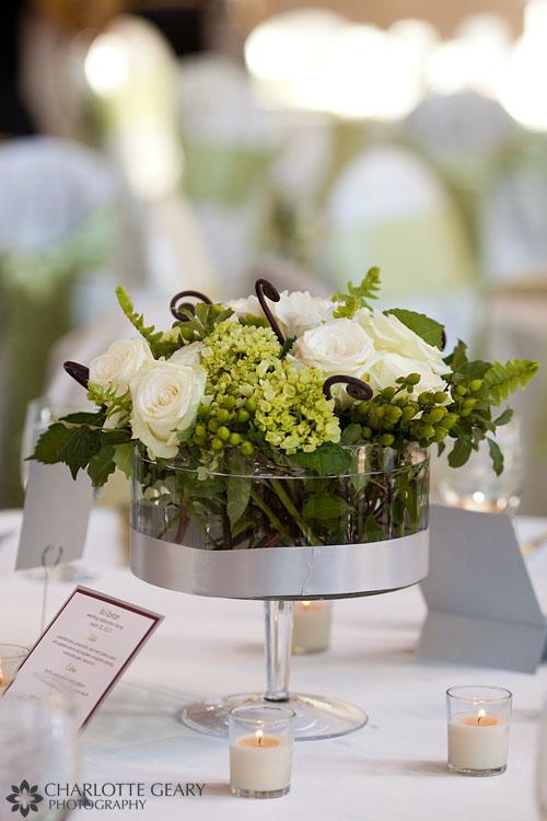 Green wedding centerpiece in a round vase