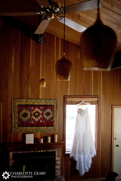 Bridal gown hanging in a window in a cabin