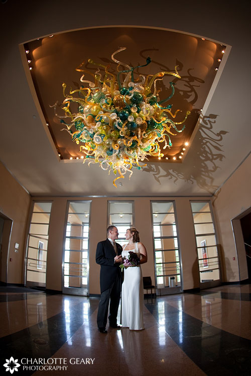 Bride and groom under a Chihuly chandelier