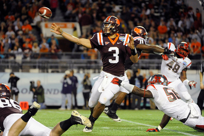 . Virginia Tech quarterback Logan Thomas, center, throws to an open receiver while under pressure from Rutgers defensive end Marvin Booker, bottom right, during the second quarter of an NCAA college football Russell Athletic Bowl game on Friday, Dec. 28, 2012, in Orlando, Fla. (AP Photo/Brian Blanco)