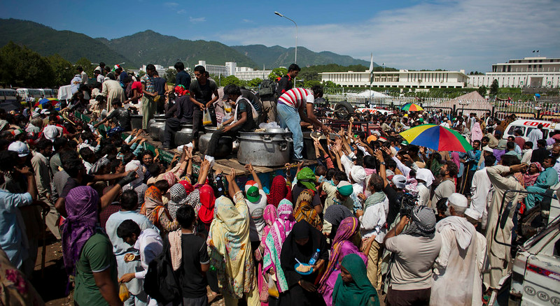 . Pakistani protesters receive food, distributed outside parliament in Islamabad, Pakistan, Monday, Sept. 1, 2014. Anti-government protesters and Pakistani police have clashed once again as the demonstrators pushed into a sprawling government complex in the country\'s capital in an effort to try to reach the prime minister\'s official residence. (AP Photo/B.K. Bangash)