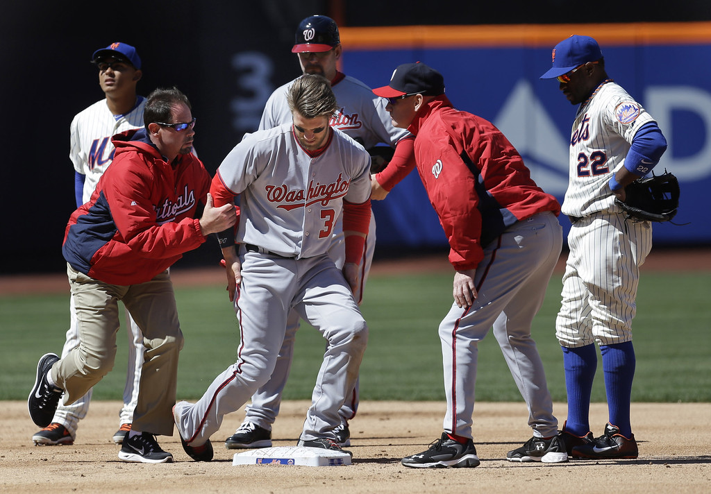 . Washington Nationals\' Bryce Harper, third from left, is helped off the field after being hit while being tagged out at second base during the second inning of the baseball game against the New York Mets on opening day at Citi Field in New York, Monday, March 31, 2014.  (AP Photo/Seth Wenig)