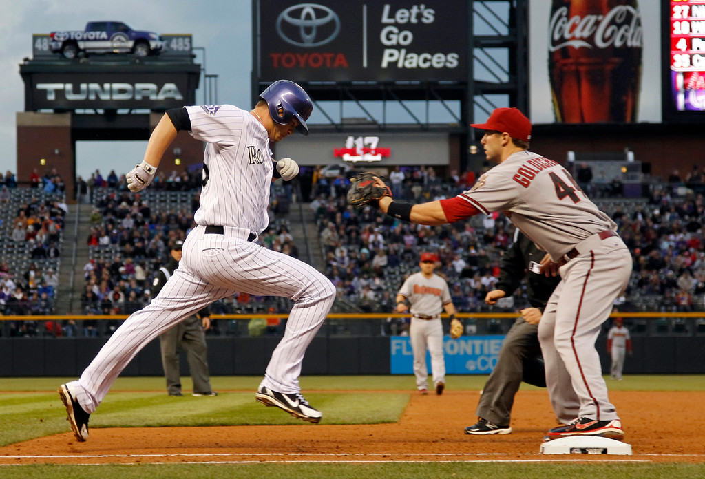 . Colorado Rockies\' Reid Brignac, left, runs to first base after putting down a sacrifice bunt as Arizona Diamondbacks first baseman Paul Goldschmidt fields the putout throw in the fourth inning of a baseball game in Denver, Saturday, April 20, 2013. (AP Photo/David Zalubowski)