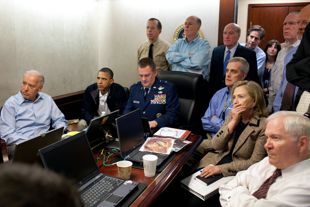 ". May 1, 2011 ""Much has been made of this photograph that shows the President and Vice President and the national security team monitoring in real time the mission against Osama bin Laden. Some more background on the photograph: The White House Situation Room is actually comprised of several different conference rooms. The majority of the time, the President convenes meetings in the large conference room with assigned seats. But to monitor this mission, the group moved into the much smaller conference room. The President chose to sit next to Brigadier General Marshall B. �Brad� Webb, Assistant Commanding General of Joint Special Operations Command, who was point man for the communications taking place. WIth so few chairs, others just stood at the back of the room. I was jammed into a corner of the room with no room to move. During the mission itself, I made approximately 100 photographs, almost all from this cramped spot in the corner. Seated in this picture from left to right: Vice President Biden, the President, Brig. Gen. Webb, Deputy National Security Advisor Denis McDonough, Secretary of State Hillary Rodham Clinton, and then Secretary of Defense Robert Gates. Standing, from left, are: Admiral Mike Mullen, then Chairman of the Joint Chiefs of Staff; National Security Advisor Tom Donilon; Chief of Staff Bill Daley; Tony Blinken, National Security Advisor to the Vice President; Audrey Tomason Director for Counterterrorism; John Brennan, Assistant to the President for Homeland Security and Counterterrorism; and Director of National Intelligence James Clapper. Please note: a classified document seen in front of Sec. Clinton has been obscured.\"" (Official White House Photo by Pete Souza)"