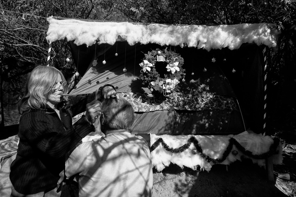 . Dorothy cuts her homeless friend, Dave Hufford\'s hair in front of her tent, which is decorated for Christmas.