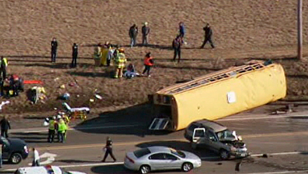 . Emergency personnel respond at the scene where a school bus overturned that was carrying about two dozen elementary school children, Friday, April 5, 2013, in Wadsworh, Ill. Lake County Sheriff\'s Office spokeswoman Sgt. Sara Balmes says there was no immediate word on any injuries. (AP Photo/Courtesy of NBCChicago.com)