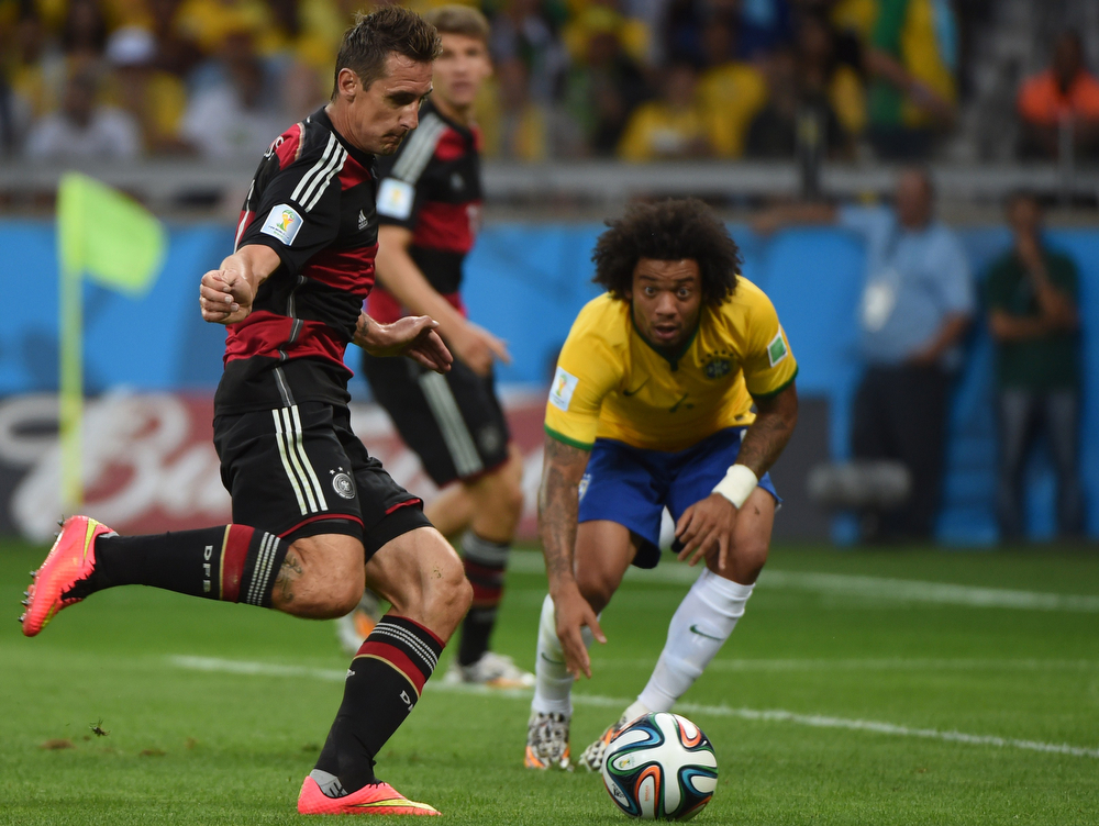 Description of . Germany's forward Miroslav Klose (L) scores the second goal as Brazil's defender Marcelo during the semi-final football match between Brazil and Germany at The Mineirao Stadium in Belo Horizonte on July 8, 2014, during the 2014 FIFA World Cup.  (PEDRO UGARTE/AFP/Getty Images)