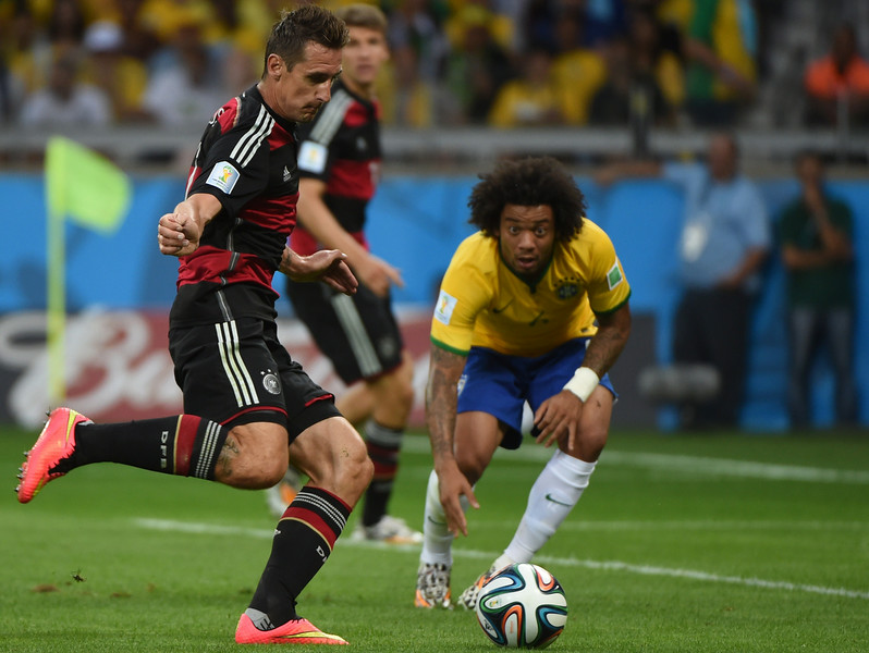 . Germany\'s forward Miroslav Klose (L) scores the second goal as Brazil\'s defender Marcelo during the semi-final football match between Brazil and Germany at The Mineirao Stadium in Belo Horizonte on July 8, 2014, during the 2014 FIFA World Cup.  (PEDRO UGARTE/AFP/Getty Images)