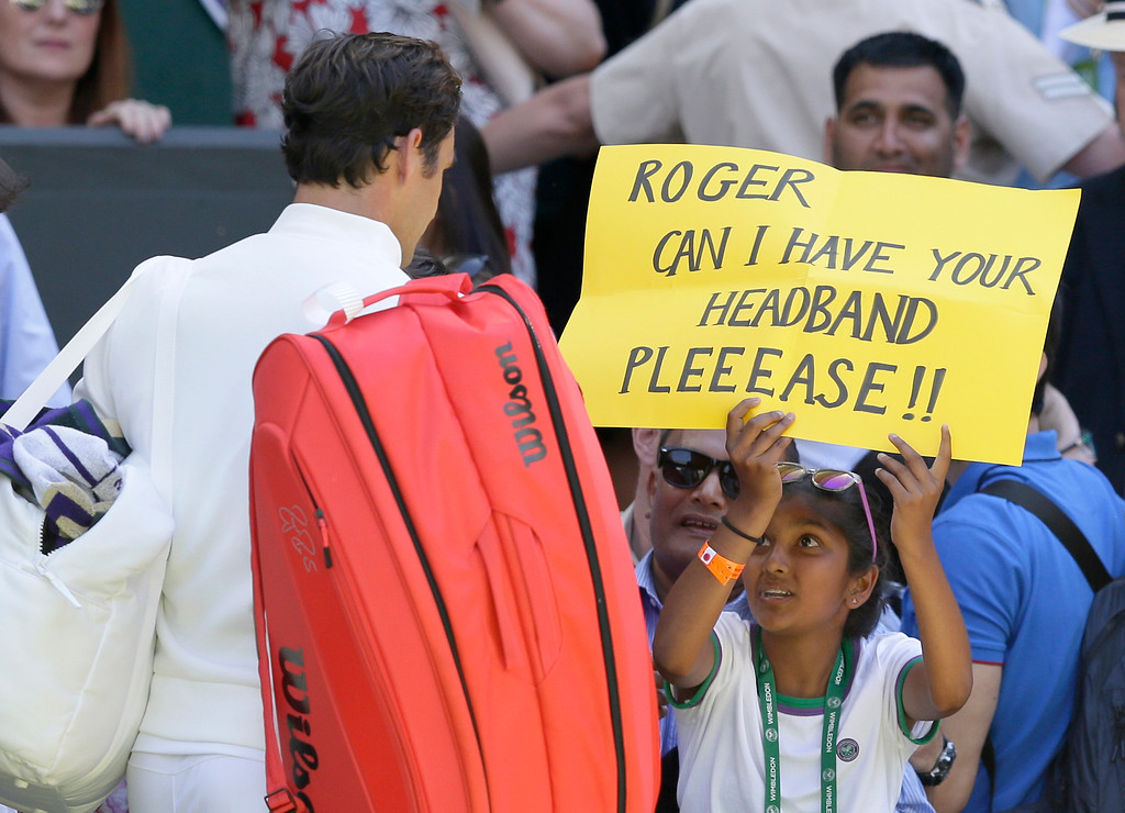 . A fan holds a banner next to Roger Federer of Switzerland, asking for his headband, at the end of his Men\'s Singles first round match against Serbia\'s Dusan Lajovic at the Wimbledon Tennis Championships in London, Monday July 2, 2018. (AP Photo/Tim Ireland)