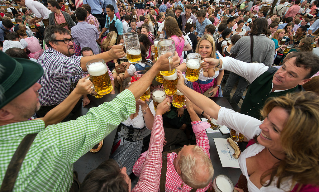 . Visitors in Bavarian style clothes raise their glasses after getting their first Oktoberfest beer in the Schottenhamel-tent at the Oktoberfest 2013 beer festival at Theresienwiese on September 21, 2013 in Munich, Germany. (Photo by Joerg Koch/Getty Images)