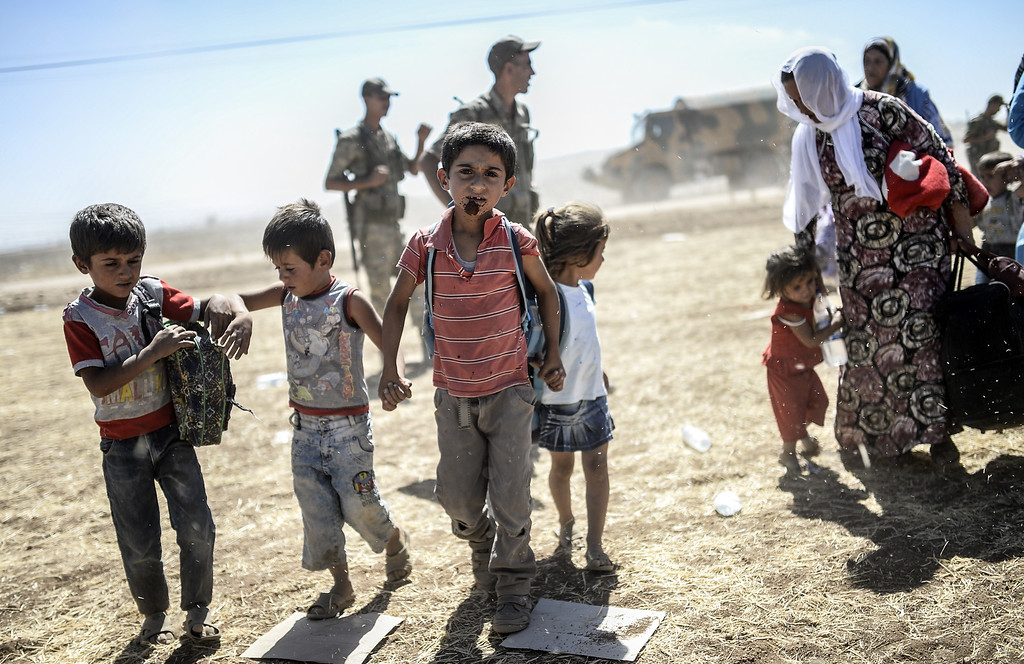 ". Syrian Kurds carry their belongings after crossing the border between Syria and Turkey near the southeastern town of Suruc in Sanliurfa province, on September 20, 2014. Several thousand Syrian Kurds began crossing into Turkey on September 19 fleeing Islamic State fighters who advanced into their villages, prompting warnings of massacres from Kurdish leaders. Turkey on September 19 reopened its border with Syria to Kurds fleeing Islamic State (IS) militants, saying a ""worst-case scenario\"" could drive as many as 100,000 more refugees into the country.  BULENT KILIC/AFP/Getty Images"
