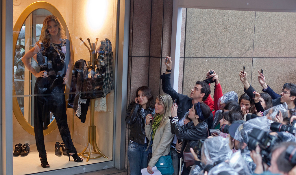 . Brazilian top model Gisele Bundchen poses for pictures inside a shop window during the launch of her women\'s clothing collection in Sao Paulo, Brazil, Thursday, April 28, 2011. (AP Photo/Andre Penner)