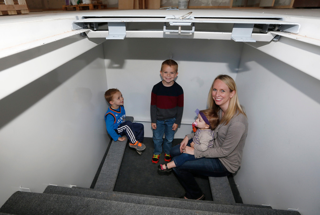 . In this Thursday, May 1, 2014 photo, Tessa Beaulieu poses for a photo in the storm shelter of her new construction home with her children, from left, Hudson, Dawson and Sloane, in Edmond, Okla.  (AP Photo/Sue Ogrocki)