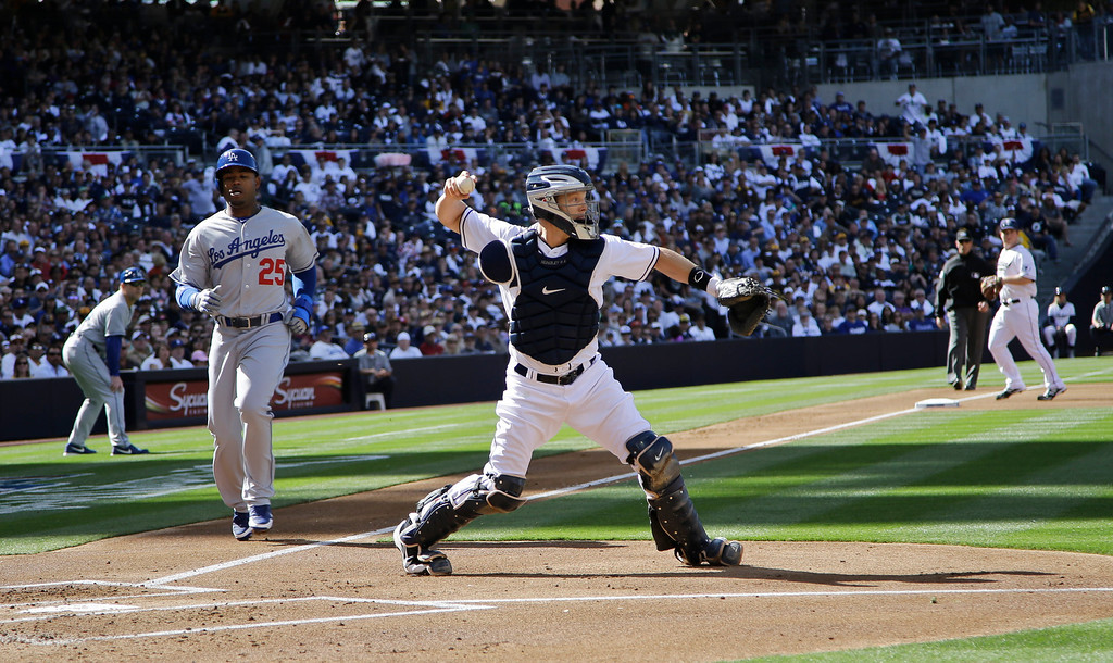 . San Diego Padres catcher Nick Hundley relays to first for a double play after forcing Los Angeles Dodgers\' Carl Crawford at home for an inning-ending double play in the first inning of a baseball game San Diego, Tuesday, April 9, 2013. (AP Photo/Lenny Ignelzi)