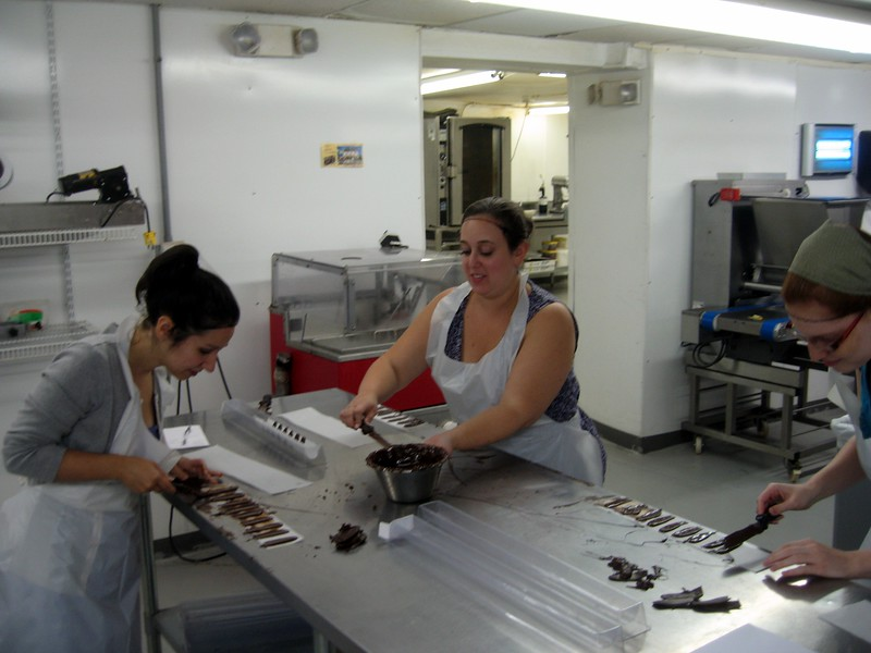 Alyssa (l), Katie, and Laura create flower petals by spreading melted chocolate on parchment paper