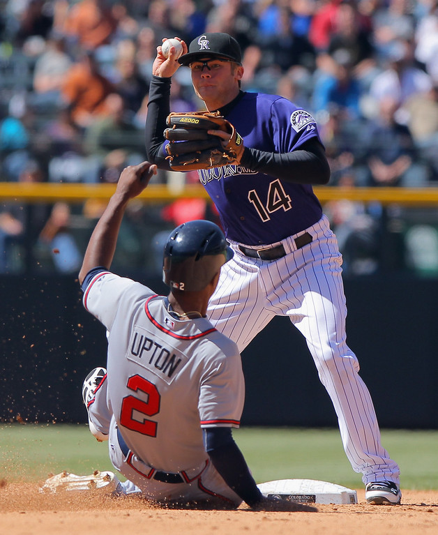 . Second baseman Josh Rutledge #14 of the Colorado Rockies turns a double play on B.J. Upton #2 of the Atlanta Braves on a ball hit by Justin Upton #8 of the Atlanta Braves at Coors Field on April 24, 2013 in Denver, Colorado.  (Photo by Doug Pensinger/Getty Images)