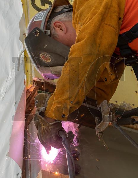 Journeyman ironworker Tony Sykora of Madlyn Metal Fab welds a steel bracket that will hold a second-story patio deck. (Josh Kulla/DJC)