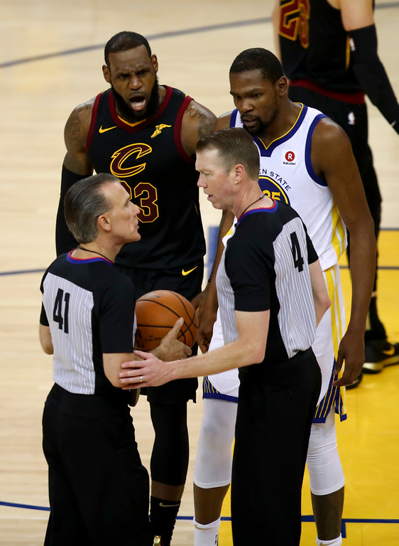 . Cleveland Cavaliers forward LeBron James, top left, and Golden State Warriors forward Kevin Durant, top right, talk with officials during the second half of Game 1 of basketball\'s NBA Finals in Oakland, Calif., Thursday, May 31, 2018. (AP Photo/Ben Margot)