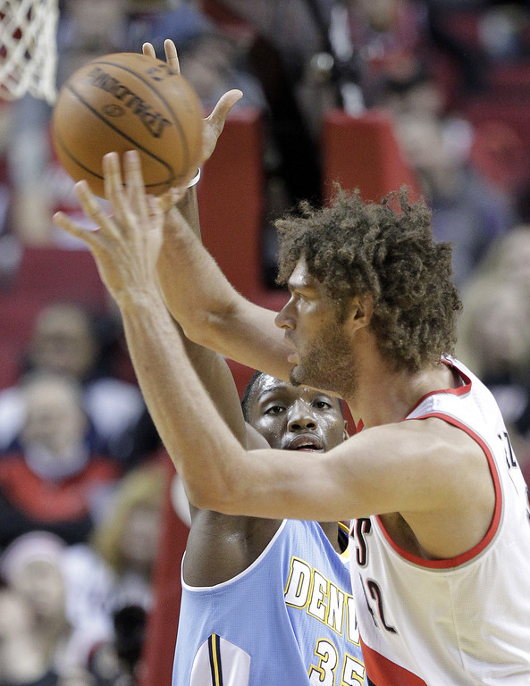 . Denver Nuggets forward Kenneth Faried, left, defends against Portland Trail Blazers center Robin Lopez during the first half of an NBA basketball game in Portland, Ore., Saturday, March 1, 2014. (AP Photo/Don Ryan)