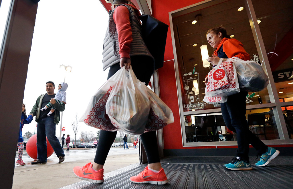. Shoppers carry their purchases as they leave Target on Black Friday, Nov. 25, 2016, in Wilmington, Mass. Stores open their doors Friday for what is still one of the busiest days of the year, even as the start of the holiday season edges ever earlier. (AP Photo/Elise Amendola)
