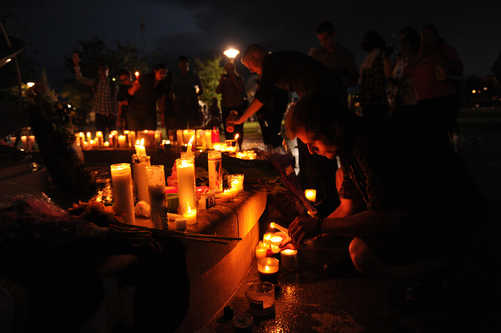 """. Josh Winn, 21, of Denver stayed after the prayer vigil for the victims of the Century 16 Theater shooting and would not let the flames die at the Aurora Municipal Center campus in Aurora, Colorado Sunday, July 22,  2012. \""""I was there. I was in the theater that night,\"""" he said. Joe Amon, The Denver Post"""