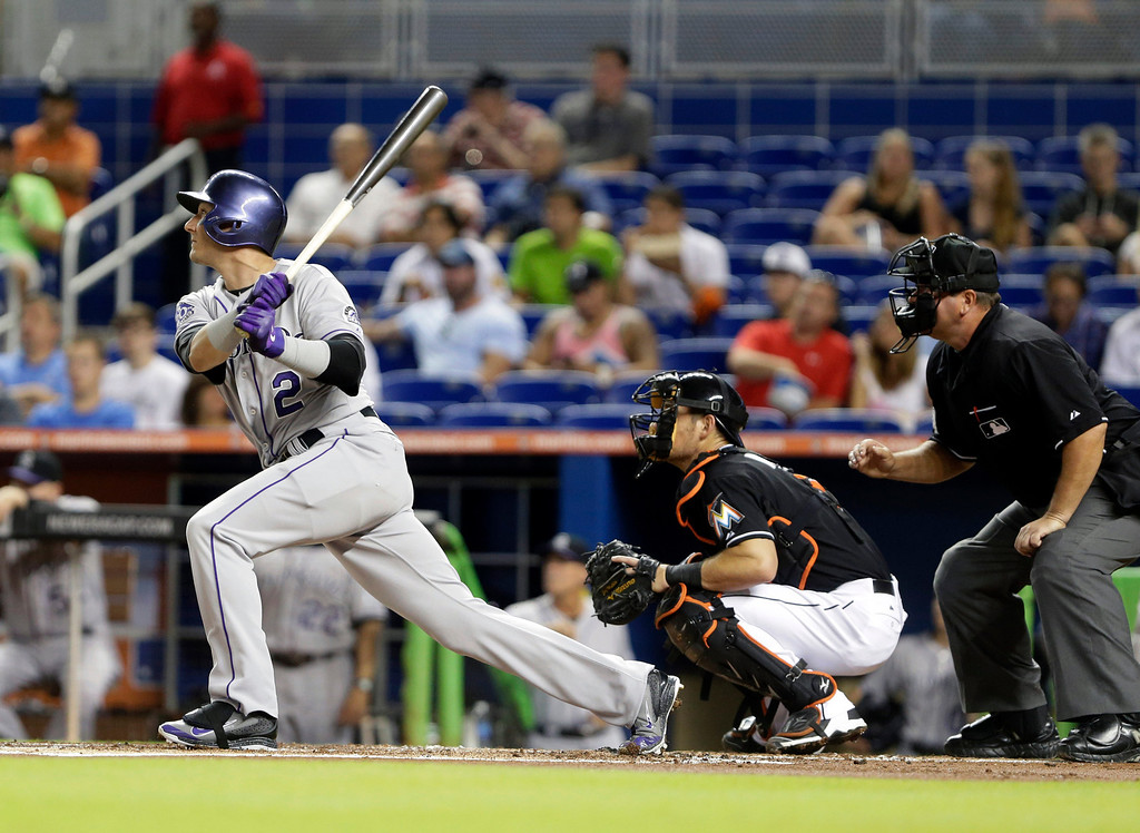 . Colorado Rockies\' Troy Tulowitzki (2) watches his ball after he hit a double during the first inning of a baseball game against the Miami Marlins, Friday, Aug. 23, 2013 in Miami. Marlins catcher Jeff Mathis, center, and home plate umpire Sam Holbrook, right, look on. (AP Photo/Wilfredo Lee)