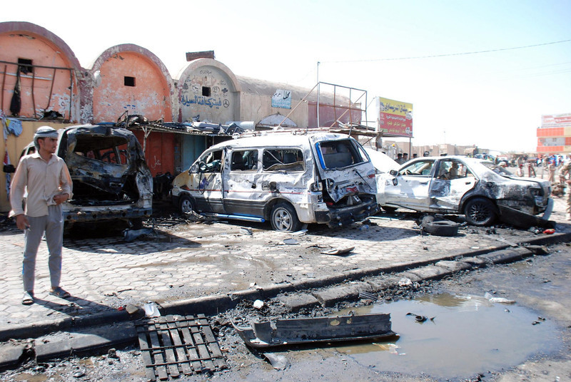 . A man stands at the site of a car bomb attack in the city of Kut, 150 km (93 miles) southeast of Baghdad, July 29, 2013. At least 10 people were killed when two car bombs blew up near a bus station in Kut, police said.  REUTERS/Jaafer Abed