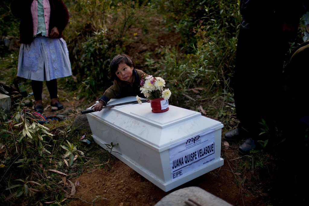 . A boy holds a machete as he plays alongside a coffin that contains the remains of Juana Quispe, during a mass burial in Chaca, Peru. Quispe is one of the Chaca residents tortured and killed on Jan. 8,1988 by Shining Path militants in retaliation for forming a self-defense committee. Their remains were exhumed in 2012 from a mass grave and released to family members on June 13, 2013.   (AP Photo/Rodrigo Abd)