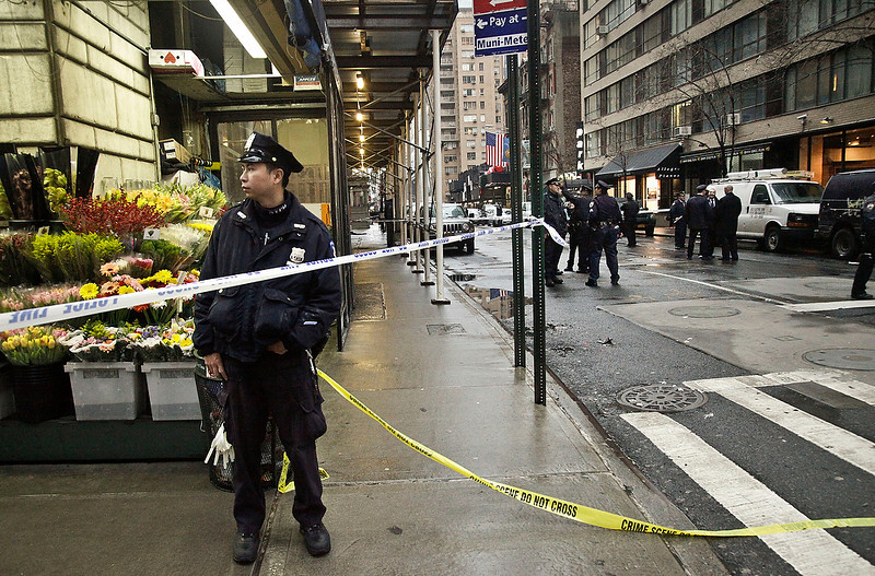 . Police secure a sidewalk during the investigation of the scene where a man was fatally shot in the back of the head on Monday Dec. 10, 2012, in New York. Authorities said the man was shot outside a school near Columbus Circle in Manhattan, lying mortally wounded in a pool of blood as the suspect escaped with a getaway driver. (AP Photo/Bebeto Matthews)
