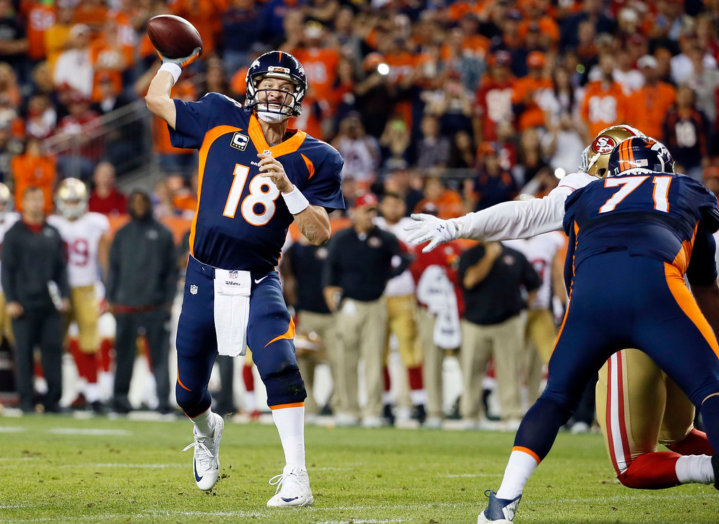 . FILE - In this Oct. 19, 2014, file photo, Denver Broncos quarterback Peyton Manning throws his 509th career touchdown pass to set the all time record during the first half of an NFL football game against the San Francisco 49ers, in Denver. Manning\'s receivers played keep-away with his milestone memento after he broke Brett Favre\'s all-time record with his 509th TD throw, an 8-yard strike to receiver Demaryius Thomas. (AP Photo/Jack Dempsey, File)