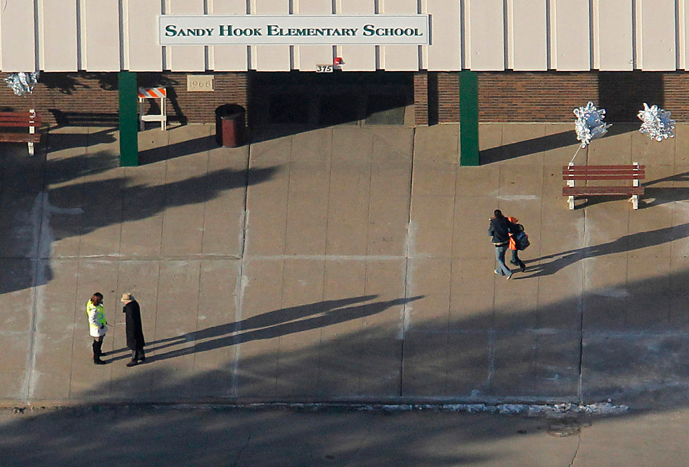 Description of . Parents escort their children into the former Chalk Hill School, a disused school refurbished specifically for the students from Newtown which now bears the name Sandy Hook Elementary School, in Monroe, Connecticut January 3, 2013. Hundreds of children who had escaped a harrowing attack on their elementary school in Newtown, Connecticut, last month, headed back to classes Thursday for the first time since a gunman had barged into their school and killed 20 of their schoolmates and six staff members. REUTERS/Carlo Allegri
