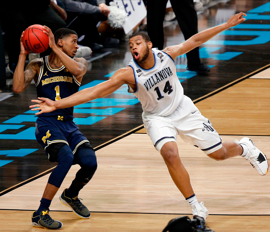 . Michigan\'s Charles Matthews (1) drives the ball against Villanova\'s Omari Spellman (14) during the second half in the championship game of the Final Four NCAA college basketball tournament, Monday, April 2, 2018, in San Antonio. (AP Photo/Brynn Anderson)