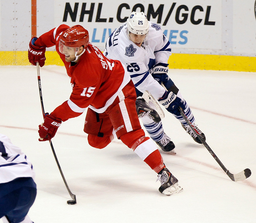 . Detroit Red Wings\' Riley Sheahan (15) is pursued down the ice by Toronto Maple Leafs\' Mike Santorelli  (25) during the third period of an NHL hockey games Saturday, Oct. 18, 2014, in Detroit. (AP Photo/Duane Burleson)
