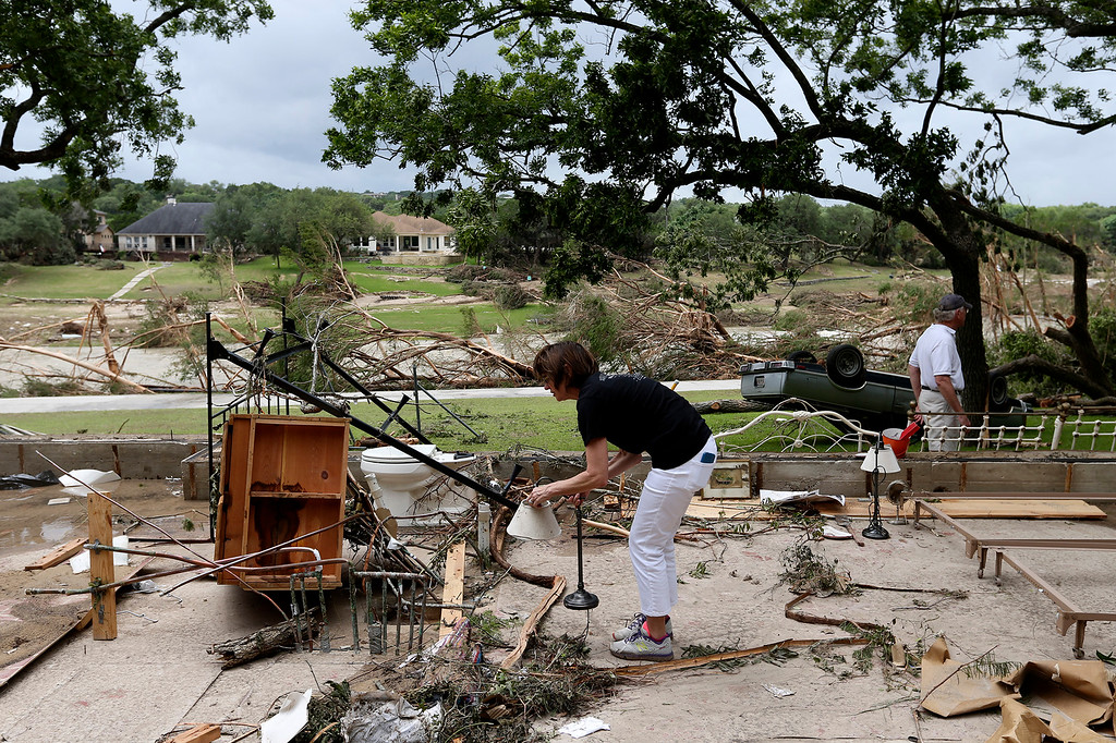 . Debi Welsh, of Corpus Christi, Texas, picks up a lamp while helping clean up the remains of her family home that washed away, Monday, May 25, 2015, in Wimberley, Texas. Around a dozen people were reported missing in flash flooding from a line of storms that stretched from the Gulf of Mexico to the Great Lakes. (Jerry Lara/The San Antonio Express-News via AP)