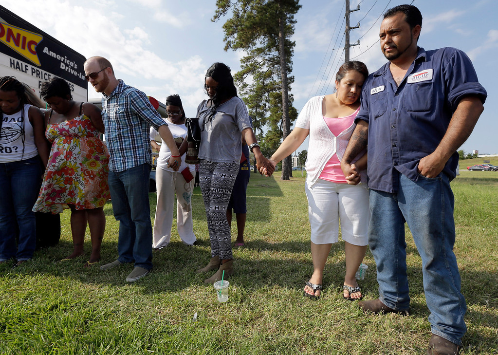 . Veronica Gonzalez, right, puts her head on the shoulder of her husband, Walter Gonzalez, as they pray while waiting for their daughter and niece outside Spring High School, Wednesday, Sept. 4, 2013, in Spring, Texas.  (AP Photo/David J. Phillip)