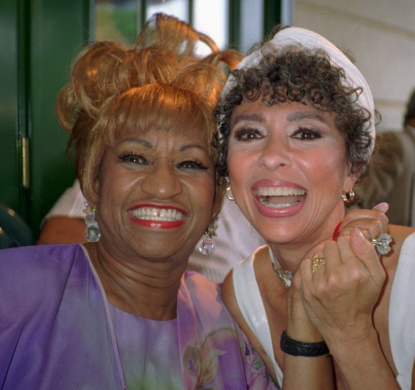 . Salsa singing queen Celia Cruz, left, and actress Rita Moreno pose for a photo at the opening celebration at four-time Grammy winner Tito Puente\'s new restaurant in New York Tuesday, July 25, 1995. (AP Photo/Aubrey Reuben)