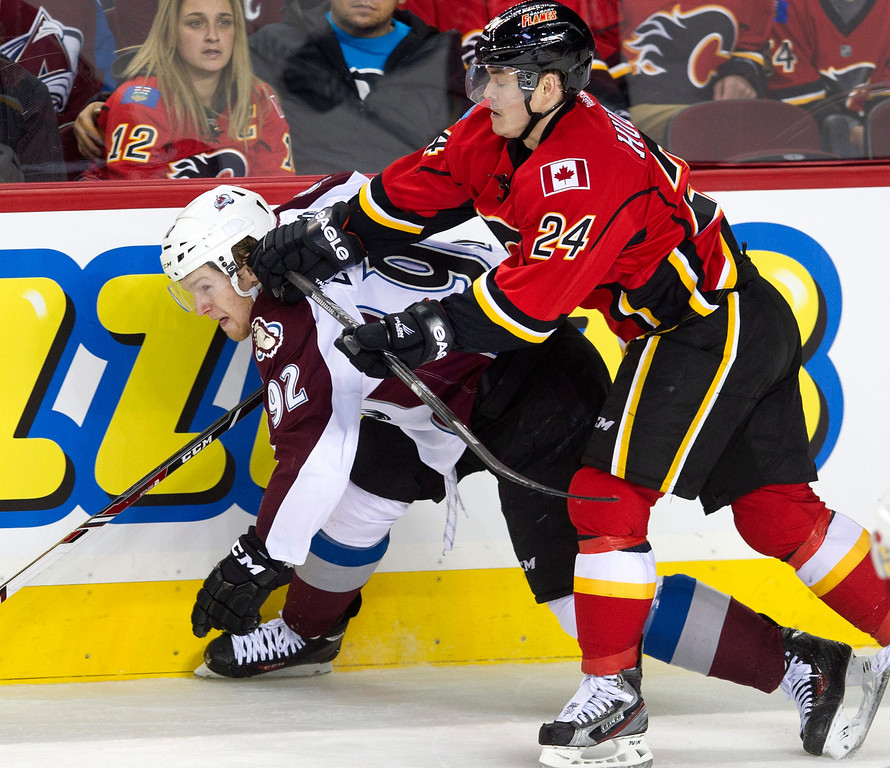 . Colorado Avalanche\'s Gabriel Landeskog, left, from Sweden, takes a hit from Calgary Flames\' Jiri Hudler, from Czech Republic, during the second period of an NHL hockey game, Friday, Dec. 6, 2013 in Calgary, Alberta. (AP Photo/The Canadian Press, Larry MacDougal)