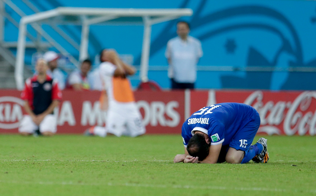 . Greece\'s Vasilis Torosidis, right, sits on the pitch after Costa Rica defeated Greece 5-3 in penalty shootouts after a 1-1 tie during the World Cup round of 16 soccer match between Costa Rica and Greece at the Arena Pernambuco in Recife, Brazil, Sunday, June 29, 2014.
