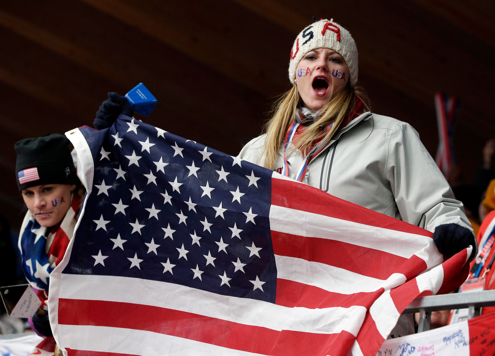 . Fans wait at the finish area during the men\'s skeleton competition at the 2014 Winter Olympics, Saturday, Feb. 15, 2014, in Krasnaya Polyana, Russia. (AP Photo/Michael Sohn)