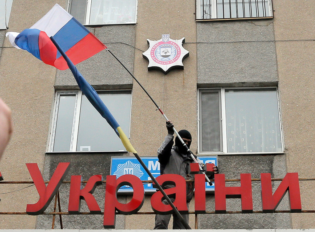 """. A pro-Russian man places a Russian flag over a police station during its mass storming in the eastern Ukrainian town of Horlivka on Monday, April 14, 2014.  The text reads: Ukrainian police station in Horlivka\"""". Several government buildings has fallen to mobs of Moscow loyalists in recent days as unrest spreads across the east of the country.  (AP Photo/Efrem Lukatsky)"""