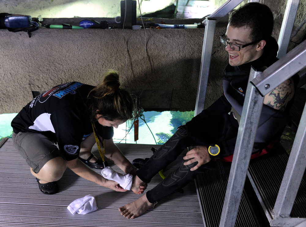 . DENVER, CO. - FEBRUARY 16: Scuba instructor Wendie Murray, left, helps Jonathan Wallace, 19, who has cerebral palsy, put on a pair of socks before his dive. Two teens from the Riley Children\'s Foundation are learning how to scuba dive with instructors from the A-1 Scuba and Travel Aquatics Center at the Downtown Aquarium.(Photo By Kathryn Scott Osler/The Denver Post)
