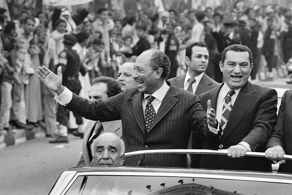 . An undated picture shows late Egyptian President Anwar Sadat (L) waving to a crowd as Vice-President Hosni Mubarak (R) laughs beside him standing in a convertible vehicle. AFP PHOTO/AFP/Getty Images