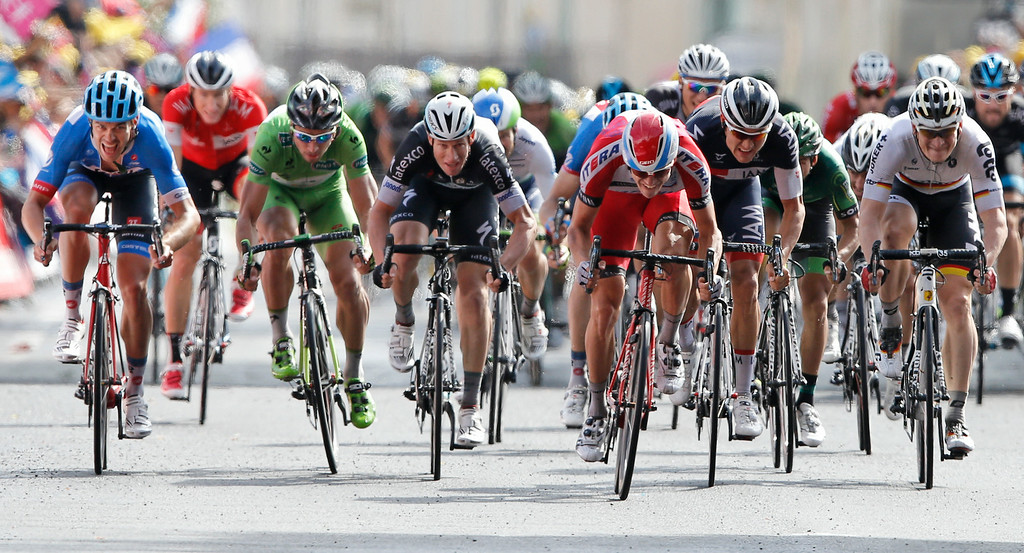 . New Zealand\'s Jack Bauer, far left, and Switzerland\'s Martin Elmiger, second left, who rode in the breakaway till the last meters of the race are caught up by the sprinting pack with celebrates on the podiums, third left, Australia\'s Mark Renshaw, fourth left, stage winner Norway\'s Alexander Kristoff, third right, Austria\'s Heinrich Haussler, second right, and Germany\'s Andre Greipel, far right, in the fifteenth stage of the Tour de France cycling race over 222 kilometers (137.9 miles) with start in Tallard and finish in Nimes, France, Sunday, July 20, 2014. (AP Photo/Peter Dejong)