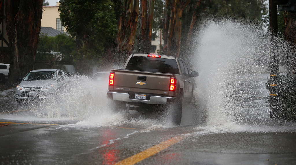 . Cars and trucks make it through a flooded El Camino Real in Burlingame, Calif., on Thursday, Dec. 11, 2014. (John Green/ Bay Area News Group)