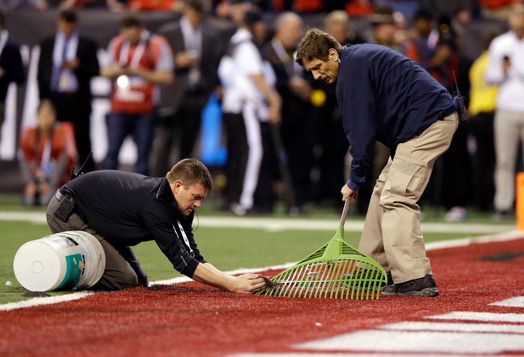 . Workers fix a problem with the artificial turf during the second half of the Big Ten championship NCAA college football game between Ohio State and Wisconsin, Saturday, Dec. 2, 2017, in Indianapolis. (AP Photo/Michael Conroy)