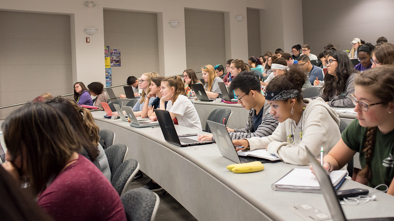 Students listen and take notes during a Biology lecture in the Engineering Building.