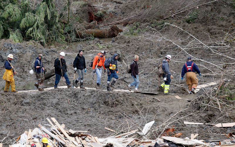 . Workers carrying hand tools walk into a debris area at the scene of a deadly mudslide, Wednesday, March 26, 2014, in Oso, Wash. Sixteen bodies have been recovered, but authorities believe at least 24 people were killed. And scores of others are still unaccounted for, although many of those names were believed to be duplicates or people who escaped safely. (AP Photo/Rick Wilking, Pool)