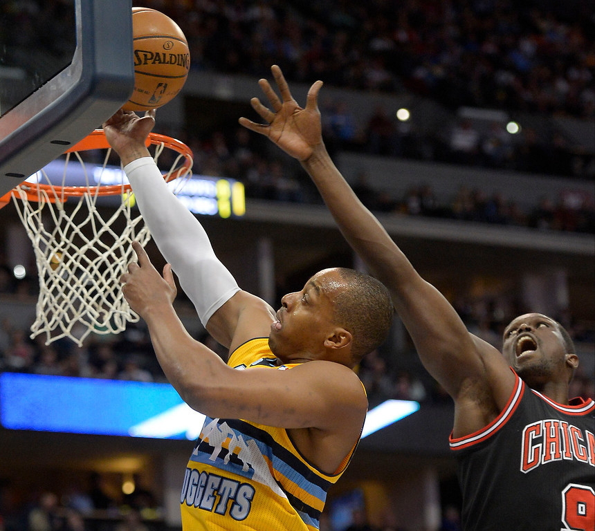 . Denver Nuggets shooting guard Randy Foye (4) drives past Chicago Bulls small forward Luol Deng (9) for a layup during the first quarter November 21, 2013 at Pepsi Center. (Photo by John Leyba/The Denver Post)