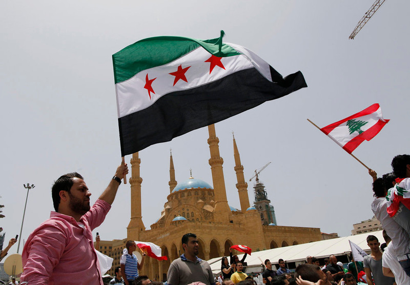 . Anti-Hezbollah activists wave Syrian opposition (L) and Lebanese national flags during a protest in Beirut June 9, 2013. A Lebanese protester was killed outside the Iranian embassy in Beirut on Sunday after gunmen from the Iranian-backed Shi\'ite militia Hezbollah opened fire when anti-Hezbollah Shi\'ite demonstrators approached, witnesses and officials said.  REUTERS/Jamal Saidi